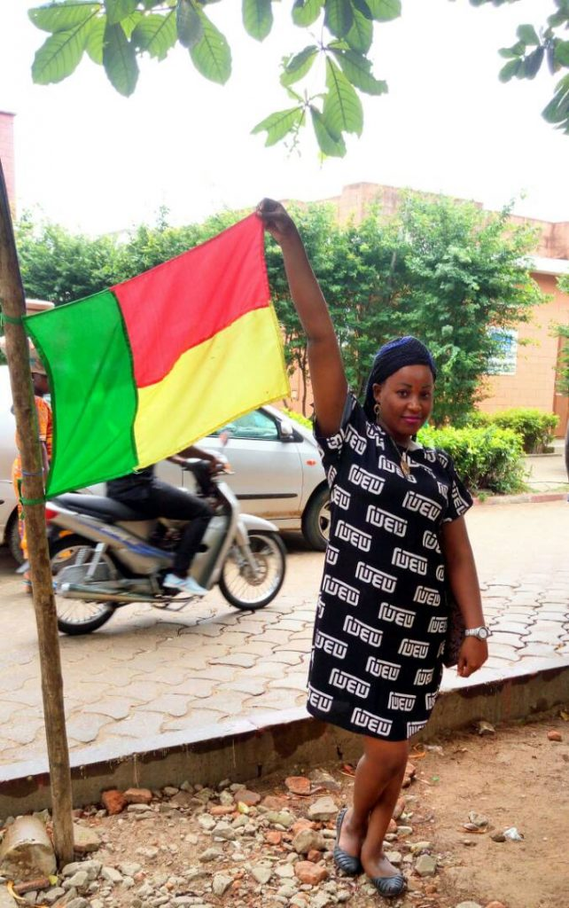 Uwomano poses with the flag of Benin republic